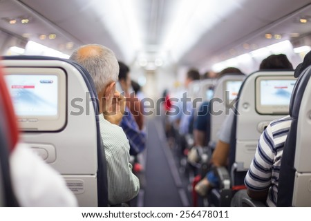 Interior of airplane with passengers on seats waiting to taik off. - stock photo