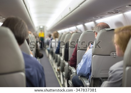 Interior of airplane with passengers on seats waiting to taik off. Stewardess in green uniform providing final safety instructions. Horizontal composition. - stock photo