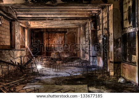 interior of an abandoned building with old chairs, lit by a ray of light - desolate and sad hall with the windows bricked - stock photo