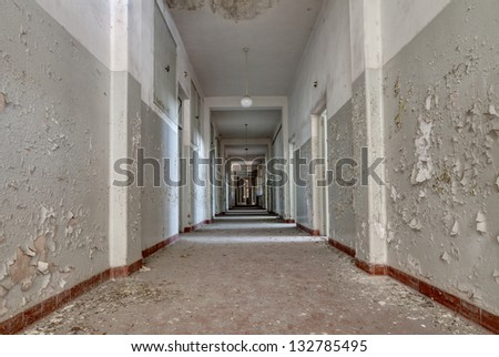 interior of an abandoned building with rubble and debris - desolate corridor of an old hospital - stock photo