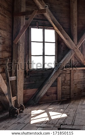 Interior of an abandoned wooden house, with light coming through the window. - stock photo