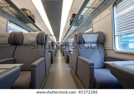 Interior of an empty first class cabin in a modern European train car, featuring luxurious gray fabric seats with head rests.