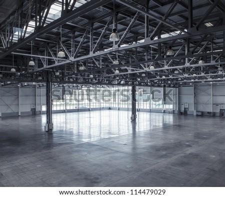 Interior of an empty warehouse with glass wall - stock photo