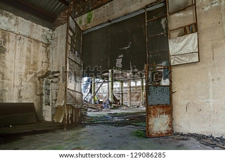 interior of an old abandoned factory with rubble and debris - ruins of an ancient industrial building - hdr image - stock photo
