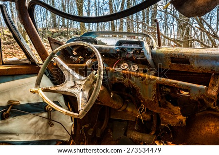 Interior of an old rusty car abandoned in a New Jersey forest (HDR look) - stock photo