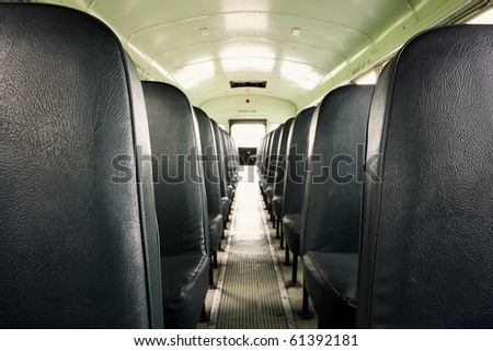 Interior of an old school bus (shallow depth of field) - stock photo