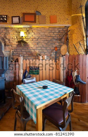 Interior of an old tavern, traditional Serbian style, souvenirs and old wooden furniture. - stock photo
