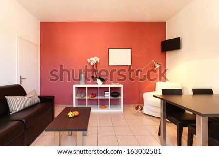 interior of apartment, living room with red wall - stock photo