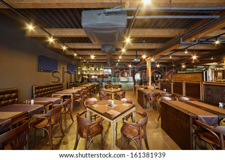 Interior of bar with wooden furniture - stock photo