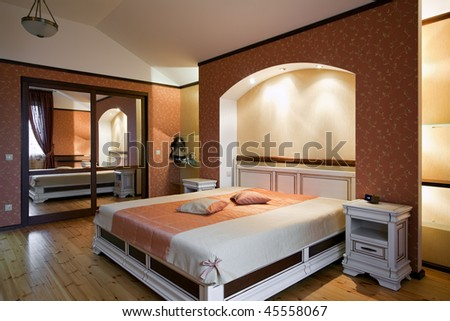 Interior of beautiful bedroom with white wooden furniture and red patterned wallpapers - stock photo
