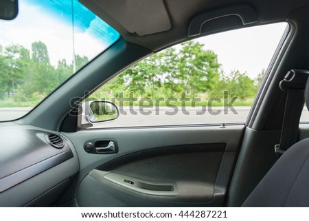 Interior of car with open window and green trees on back