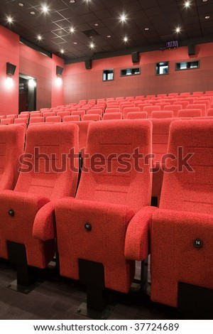 Interior of cinema auditorium with lines of red chairs.
