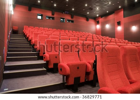 Interior of cinema auditorium with stairs and lines of red chairs.
