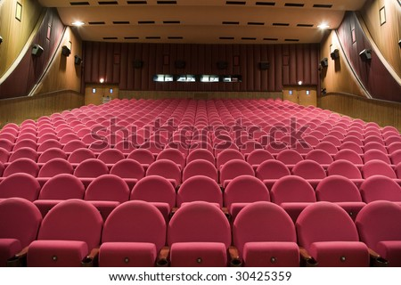 Interior of cinema auditorium with walls and ceiling decoration and line of pink chairs.