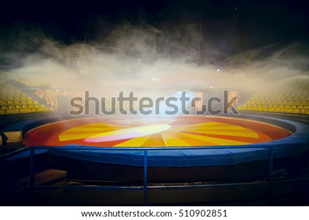 Interior of circus - arena with effect of fog and rows of chairs for people