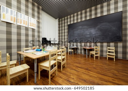 Interior Of Classroom With Blackboard On Wall And Wooden Furniture In Children Club