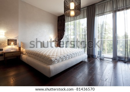 Interior of designer bedroom with beautiful view from window - stock photo