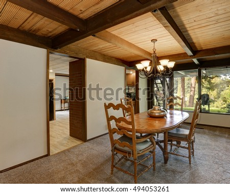 Interior of dining room in large wooden house. Close up of carved wooden chairs with cushions and solid dining table. Northwest, USA