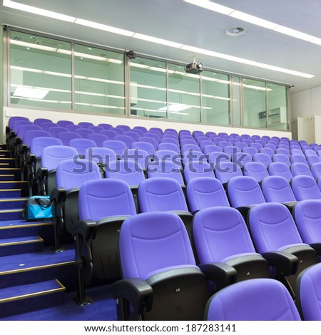 Interior of empty conference hall with purple velvet chairs. - stock photo