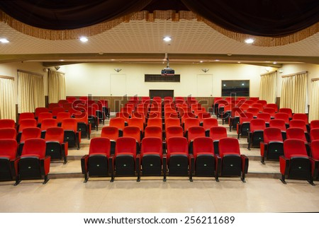 Interior of empty conference hall with red chairs - stock photo