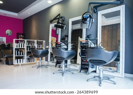 Interior of empty modern hair and beauty salon decorated in gray and fuchsia colors - stock photo