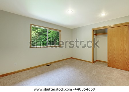Interior of empty room with closet, beige carpet floor, white walls and small window. - stock photo