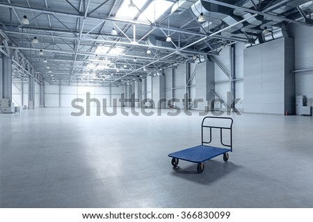 Interior of empty warehouse with a cart