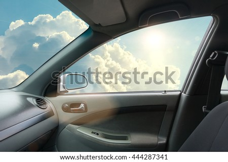 Interior of fly car with open window and sky on side - stock photo