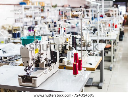 Interior of garment factory shop. Closes making atelier with several sewing machines. Tailoring industry, fashion designer workshop, industry concept