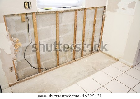 Interior of kitchen with drywall torn out because of water damage and the resulting mold. - stock photo