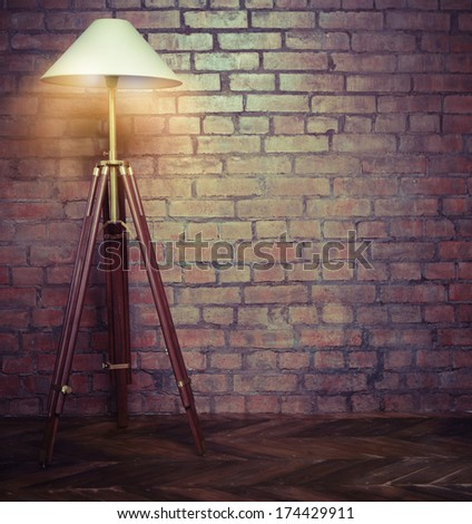 Interior of loft with retro lamp over brick wall - stock photo