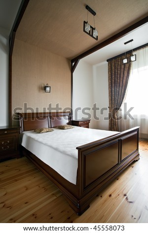 Interior of luxury bedroom in daylight with window - stock photo