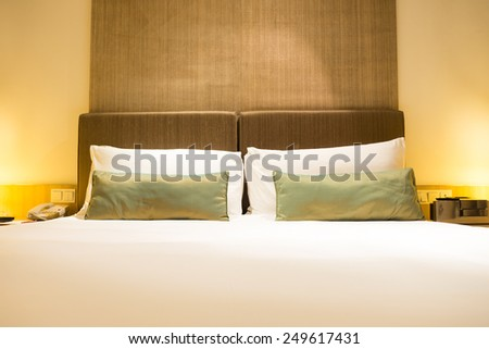 Interior of luxury double beds in hotel bedroom - stock photo