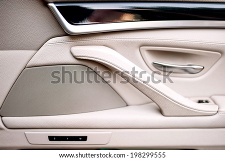 Interior of modern car as background with close-up of doors and manufacturing details. High quality beige and white leather, wood and aluminum.