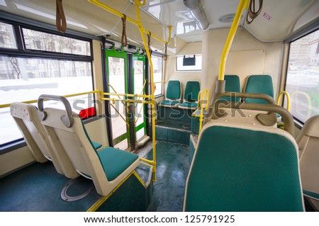 Interior of modern city articulated bus. Back side of bus with seat places and door