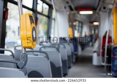 Interior of modern city tram with electronic ticket validation machine - stock photo