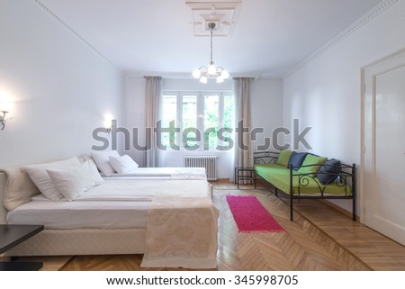 Interior of modern comfortable hotel room with double bed and green sofa - stock photo