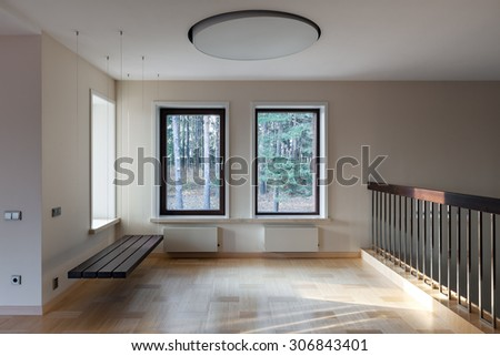Interior of modern empty space with suspended bench and big windows - stock photo