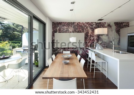 Interior of modern house, beautiful open space, kitchen and dining table - stock photo