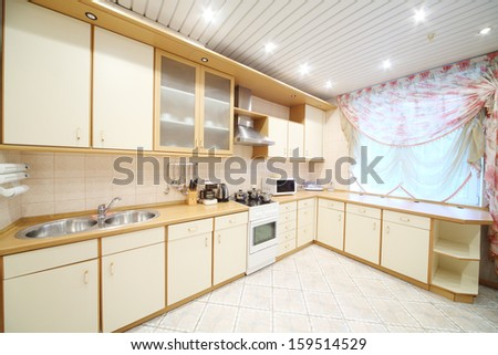 Interior of modern kitchen with beige furniture and a stove - stock photo