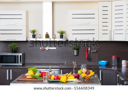 Interior of modern kitchen with fruits and vegetables on the table