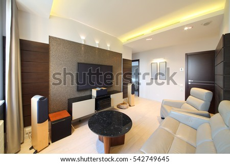 Interior of modern living room with a home theater and a leather sofa and armchair