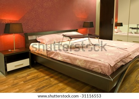 Interior of modern red bedroom with furniture and lamps - stock photo
