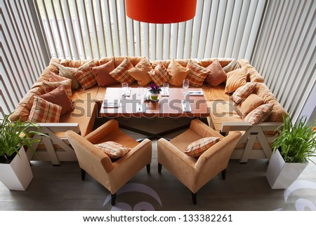 Interior of modern restaurant with a big orange sofa two orange chairs, an orange lamp and the laid table.Top view - stock photo