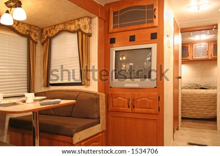 interior of motor home with dining table and dishes, tv, covered windows, and bedroom showing - stock photo