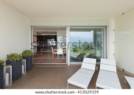 Interior of new apartment, veranda with two sunbeds - stock photo
