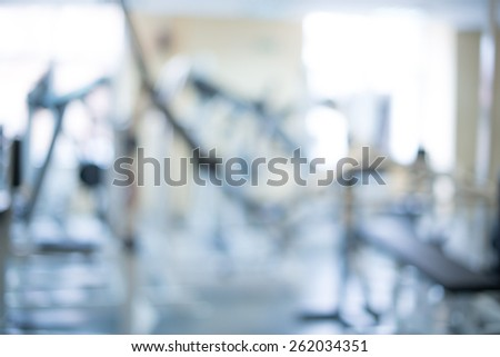 interior of new modern fitness center gym with equipment, abstract blur background - stock photo