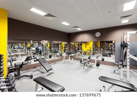 Interior of new modern gym with equipment - stock photo