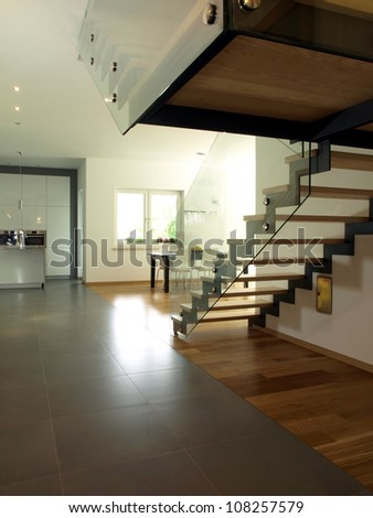 Interior of new modern house, stairs and kitchen - stock photo