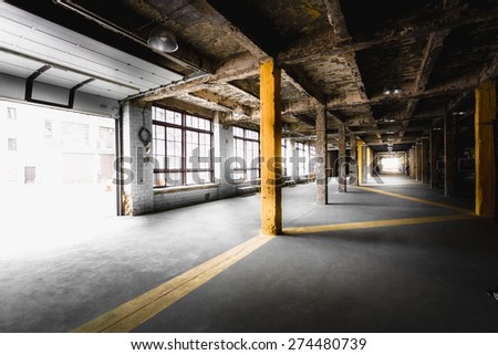 Interior of old abandoned factory hallway with big windows - stock photo